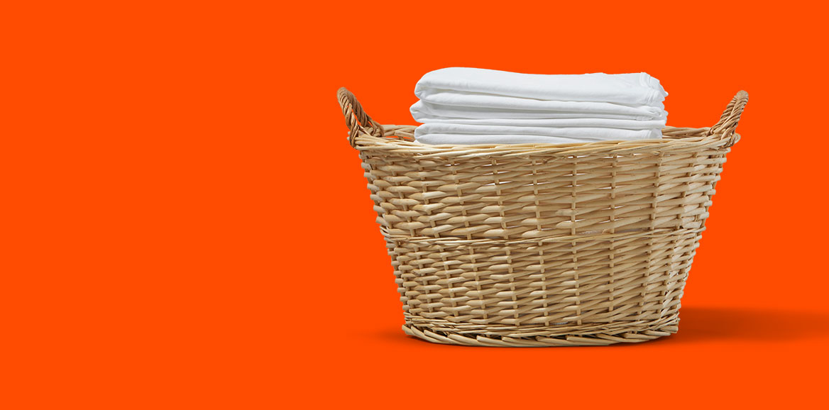 Folded white clothes in a woven laundry basket