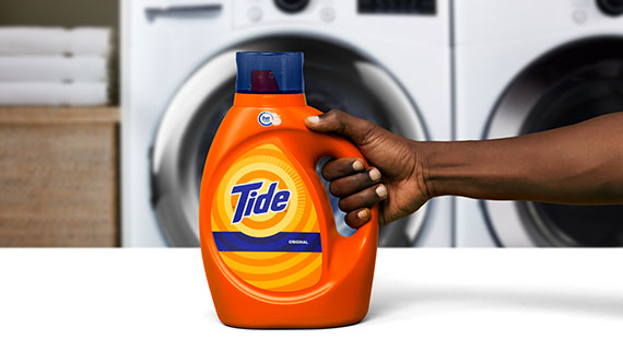 A person holding Tide liquid laundry detergent