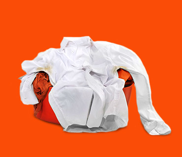 A white shirt with a sweat stain on the top of a laundry basket