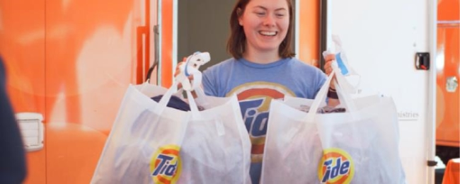 A woman handing out two bags of clothes cleaned with Tide