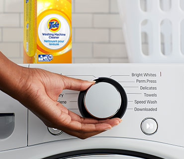 A person selecting the wash cycle on a washing machine