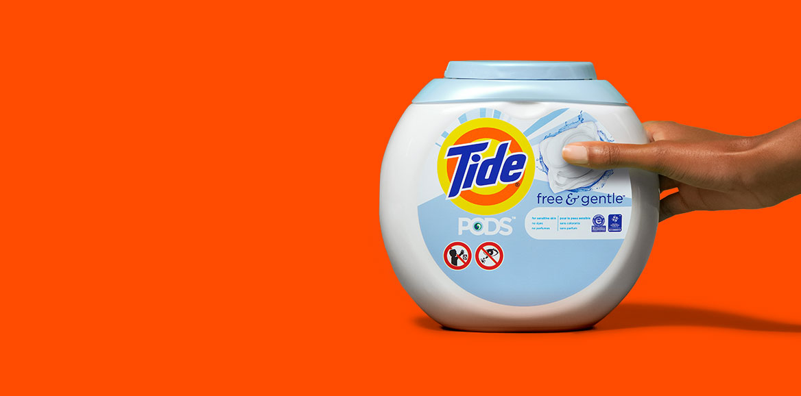 A person holding a Tide PODS Free and Gentle product