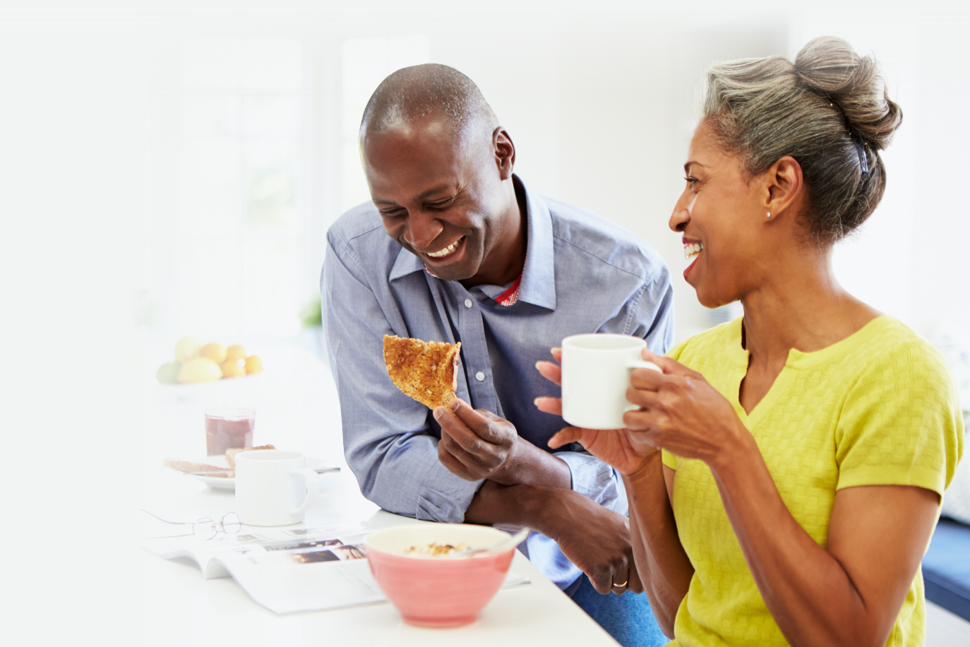A couple in their 50s are laughing and smiling over breakfast, as they have found a great community and answers on the Fixodent website.