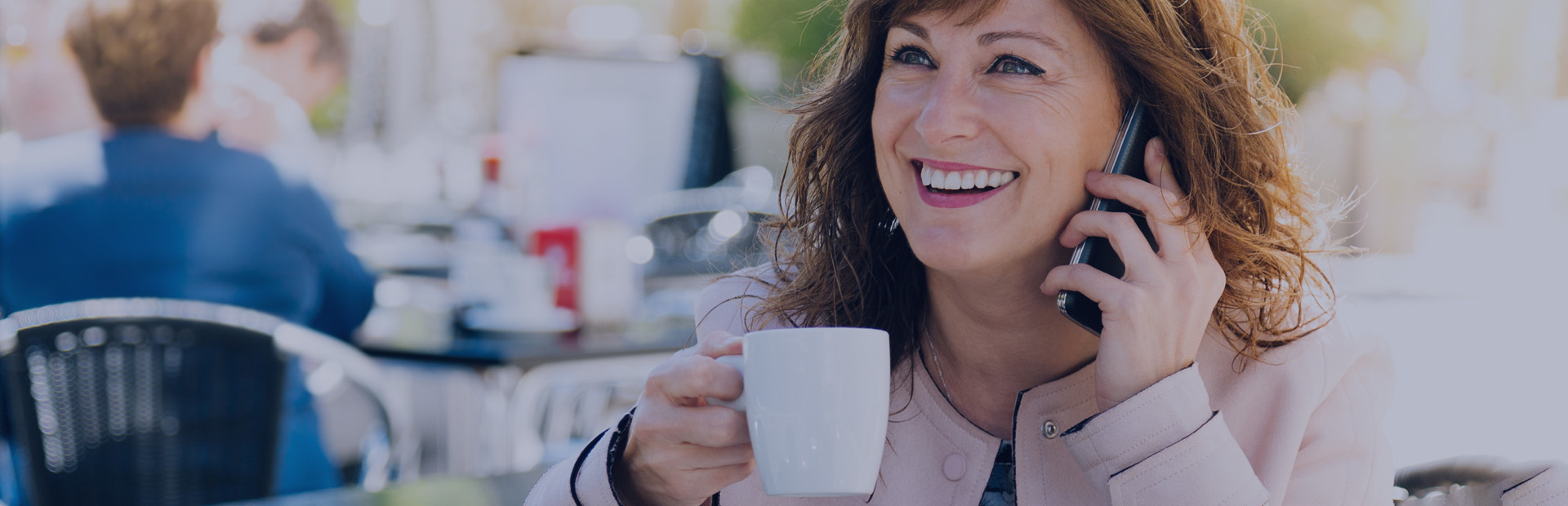 A woman in her 50s is smiling with a cup of coffee as she understands what complete dentures are thanks to Fixodent.
