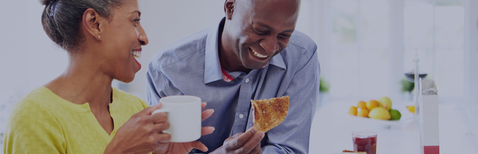 A couple in their 40s are laughing over breakfast as they feel secure in making the decision to choose between dentures or implants thanks to Fixodent.