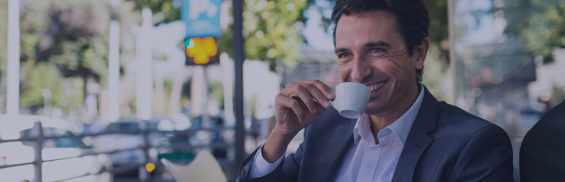 A man in his 40s sips an espresso on an outdoor terrace with a smile, as he knows how to remove stains from dentures thanks to Fixodent.