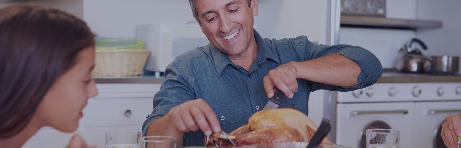 A man in his fifties is carving into a roast chicken, he is smiling because he knows he won't have any issues eating with dentures thanks to Fixodent's tips.