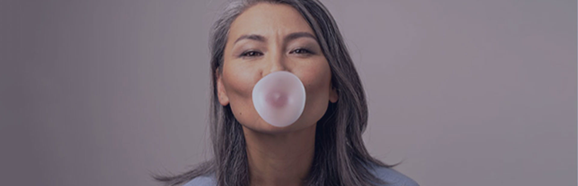 A woman in her 50s blows some bubble gum, as she knows she can still chew gum with dentures while using Fixodent.