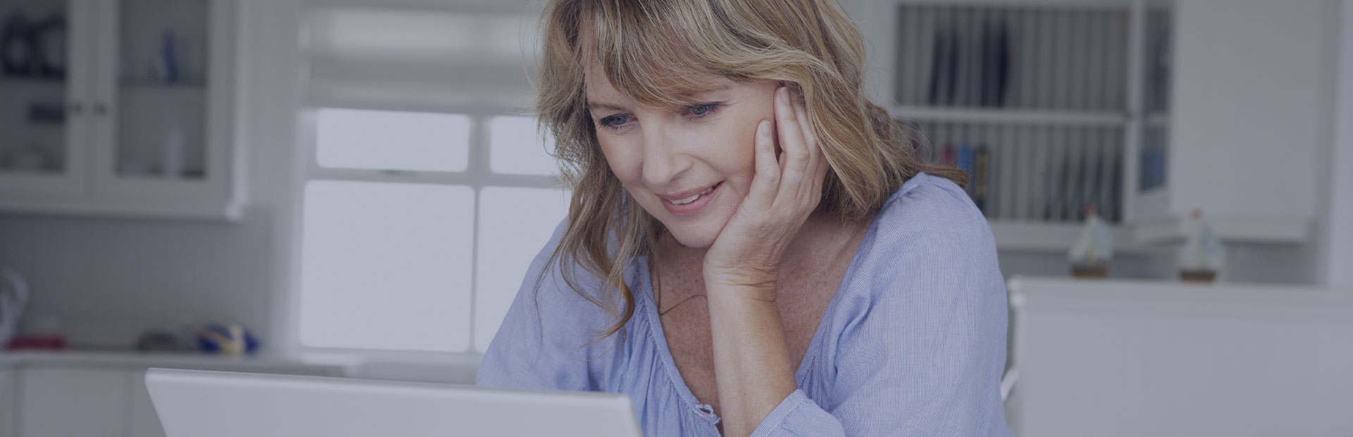 A woman in her early 50s is on her laptop in the kitchen, researching what she can do about denture pain and sores.