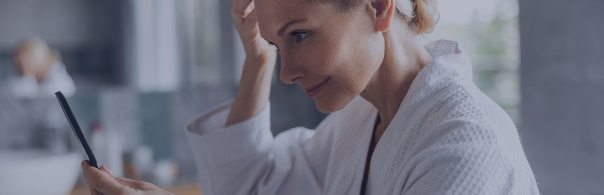 A woman in her 50s in a white dressing gown looks into a mirror confidently, as she knows how to shift the focus from her dentures.