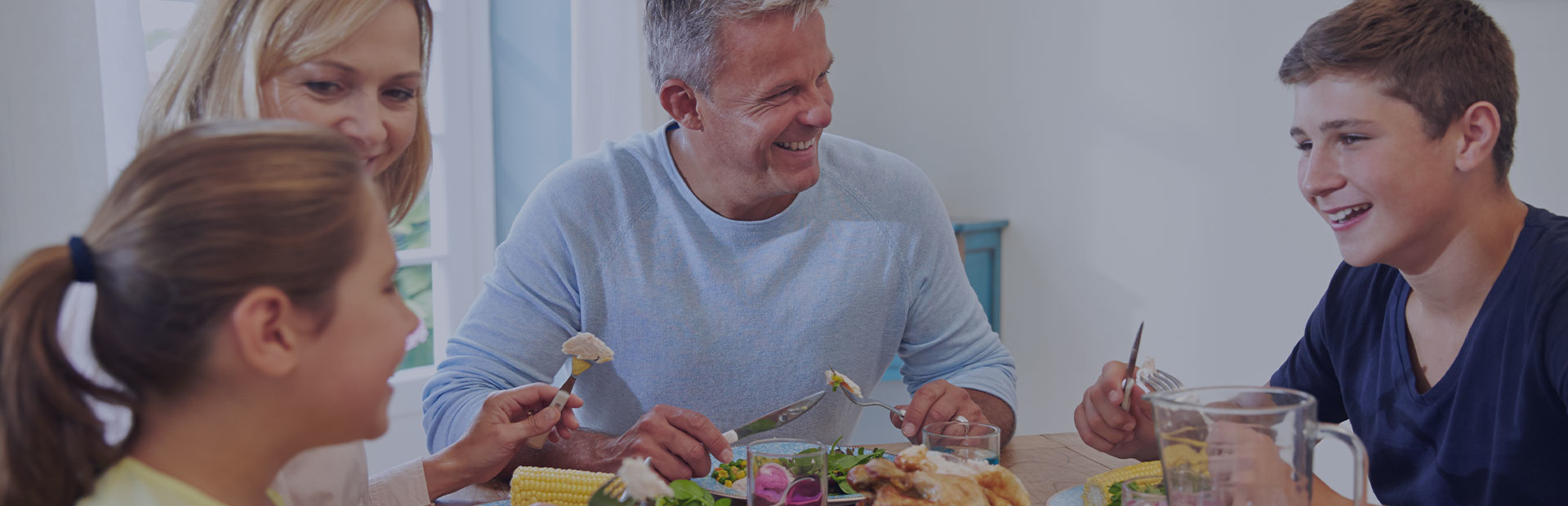 A family sit around the table eating dinner, the father has dentures but is smiling confidently and eating meat and corn on the cob, as he knows about the benefits of denture adhesive cream.