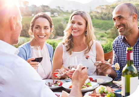 A group of friends are sitting around a table in a garden overlooking the hills, they are drinking wine, eating and smiling, as even the ones with dentures know he won't have issues eating with dentures, thanks to Fixodent.