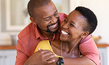 A couple in their 40s are hugging and smiling, the woman is wearing dentures, but is happy and confident as she has learned everything she needs to know about denture adhesive thanks to Fixodent.
