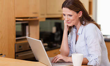 A woman in her 40s is in a wood-clad kitchen on her laptop reading the answers to the most frequently asked questions on Fixodent.