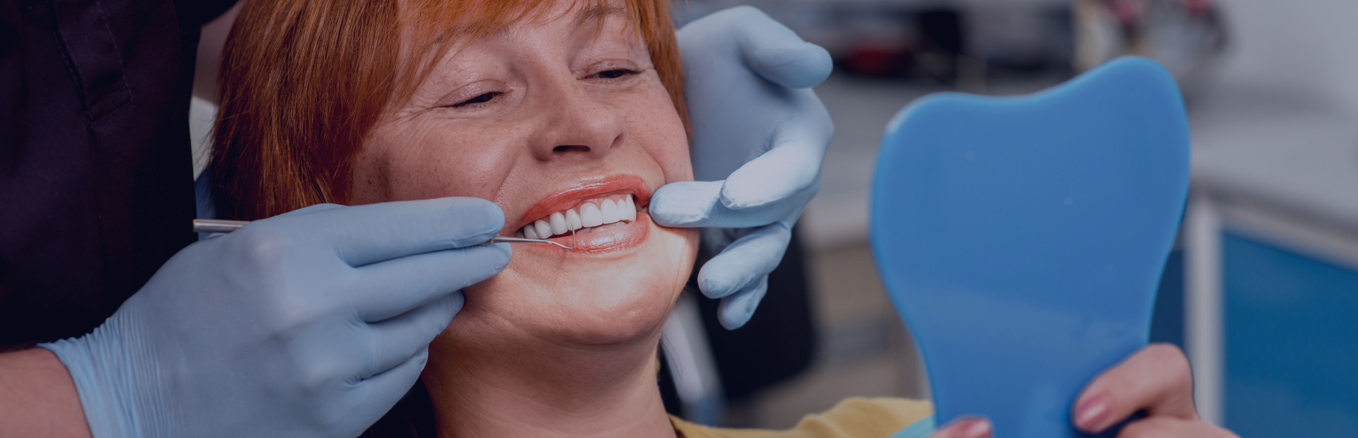 A woman in her 60s is in the dentist's chair smiling, because she knows the correct cleaning and maintenance procedure for her dentures.