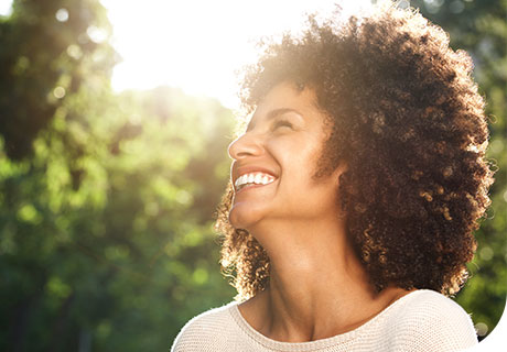 A woman in her forties is in a sunny garden and smiling as she thinks about choosing to get dentures or dental implants.
