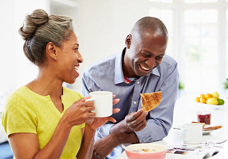 A couple in their forties are having breakfast in a bright white kitchen and are discussing the types of dental implants right for them.