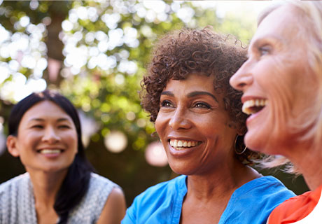 A group of female friends aged fifty and are outside in a park, smiling and laughing as they discuss how much do dental implants cost.