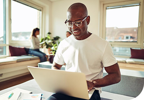 A man in a white t-shirt and glasses sits on a table edge with his laptop researching about the levels of zinc in denture adhesive.