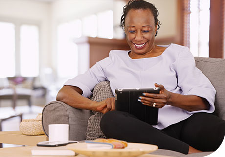 A woman in her forties is sitting in her living room smiling as she researches the topic on what are partial dentures on her tablet.