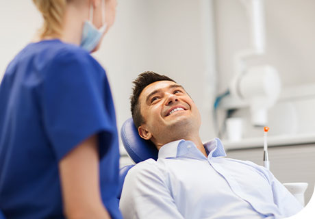 A man in his thirties is lying in the dentist chair while a female dentist explains to him the difference between temporary and permanent dentures.