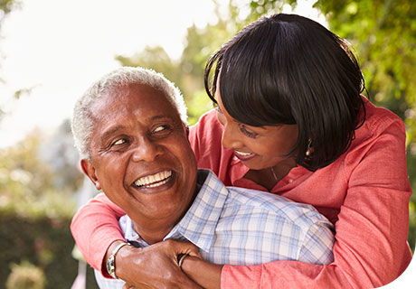 A couple in their fifties are hugging and smiling in a garden, the man is smiling with confidence, thanks to immediate dentures.