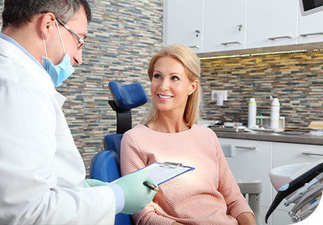 A woman is sitting in the dentist chair with her dentist explaining to her the reasons and solutions for ill fitting dentures.