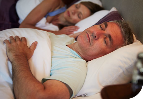 A couple in their fifties are sleeping, the man looks relaxed because he knows he should not sleep in dentures.