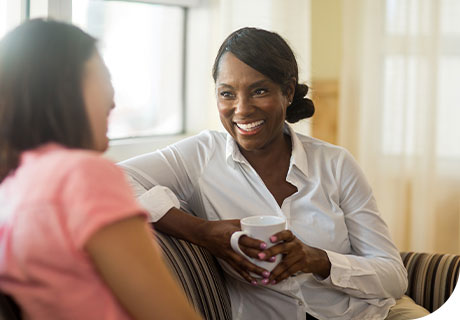 Two women are sitting on a striped sofa by the window having a conversation, one is smiling with a brilliant grin, confident she knows how to speak with dentures.