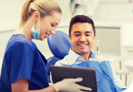A dentist holds a tablet in her hand showing the screen to her patient, while she answers his frequently asked questions about denture adhesive.