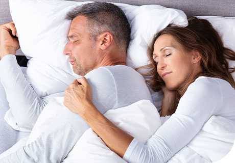 A couple in their 30s are sleeping soundly, as they know that their dentures need a rest at night after being held in place all day by Fixodent.