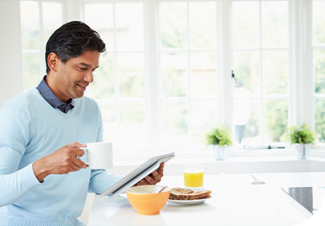A man in his 40s is sitting in a white kitchen drinking a coffee and having breakfast while reading a brochure on the costs of getting detures.