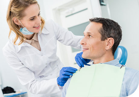 A dentist explains the denture-related dental procedures to a smiling male patient, who sits in a dental chair.