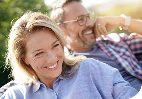 A couple are outdoors smiling in the sun, as they are getting used to wearing new dentures.