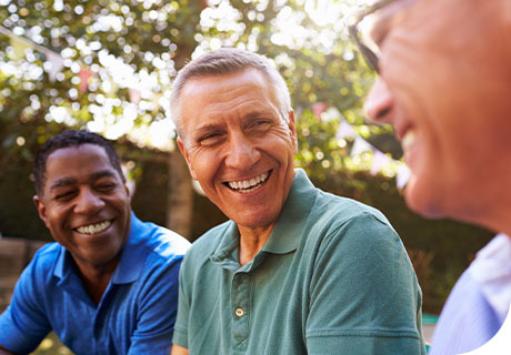 A group of male friends in their fifties are smiling in a garden, as they discuss getting used to full or partial dentures.