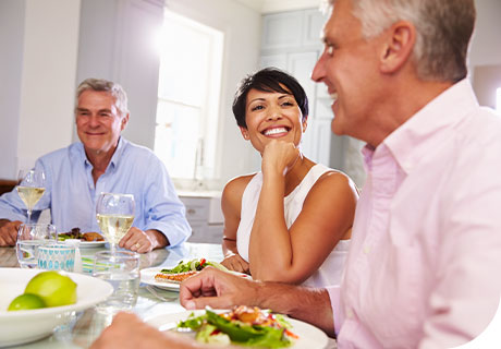 Two men and a woman in their fifties are sitting around the table chatting. The woman has a confident smile as she has no concerns about smiling with dentures.
