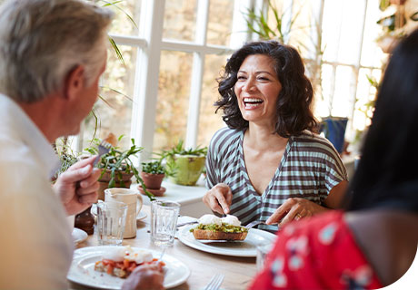 At a dinner party, a woman across the table from a man asks him some frequently asked questions about eating with dentures after recently getting some herself.