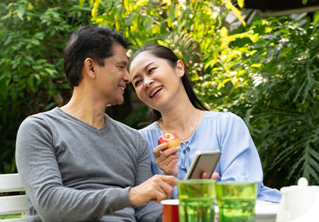 A couple in their forties are sitting in a park enjoying a meal together, the woman shows the man her phone with tips on how to eat healthily with dentures.
