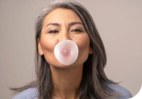 A woman is seen blowing bubble gum, showing you can chew gum with dentures.