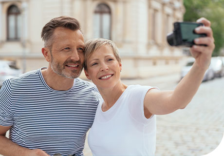 A couple are in a park taking a selfie of themselves, they both have white, brilliant smiles, and even though one of them has dentures, they feel beautiful.