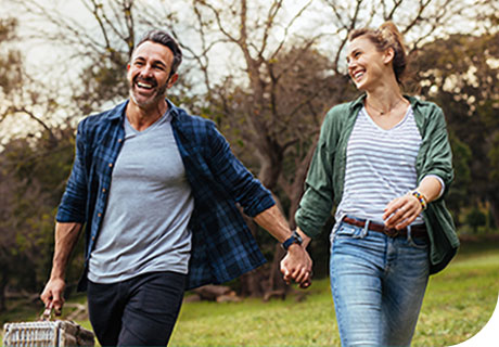 A couple are walking through a park holding hands and smiling, as they learn to live a healthy lifestyle with dentures.