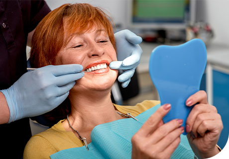 A close-up of a woman in the dentist's chair looking in the mirror at her new dentures, while her dentist explains how long do dentures last.
