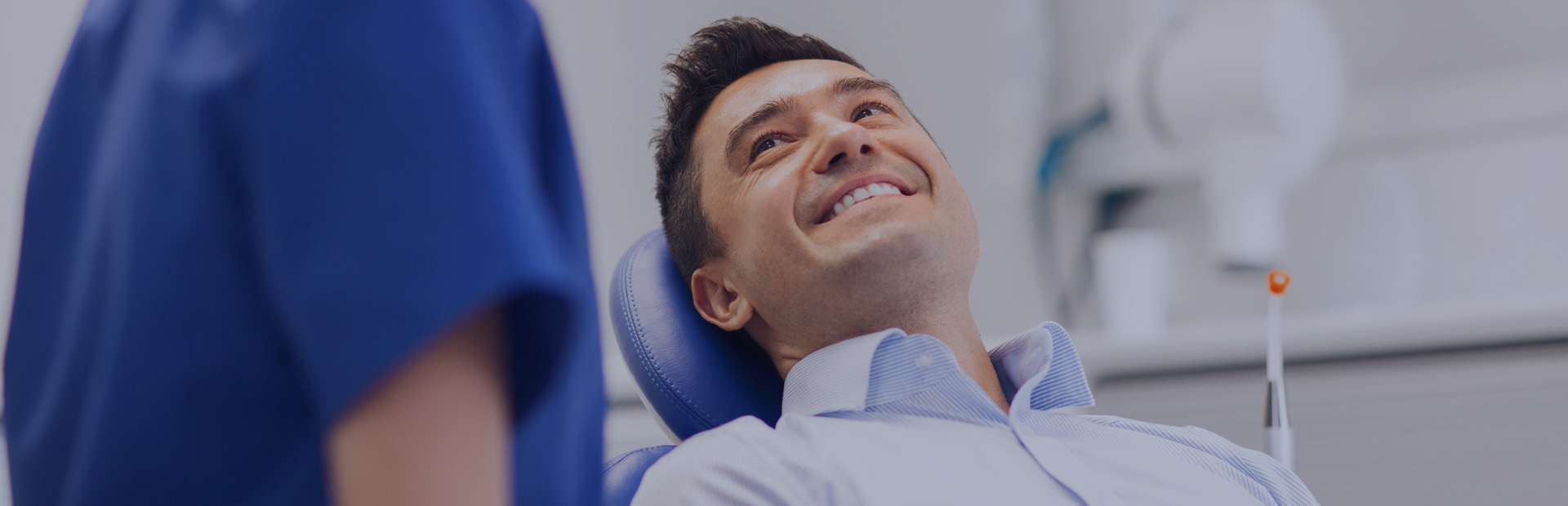 A man in his 30s smiles in the dentist's chair as the dentist explains the best way to remove dentre adhesive from mouth gums.