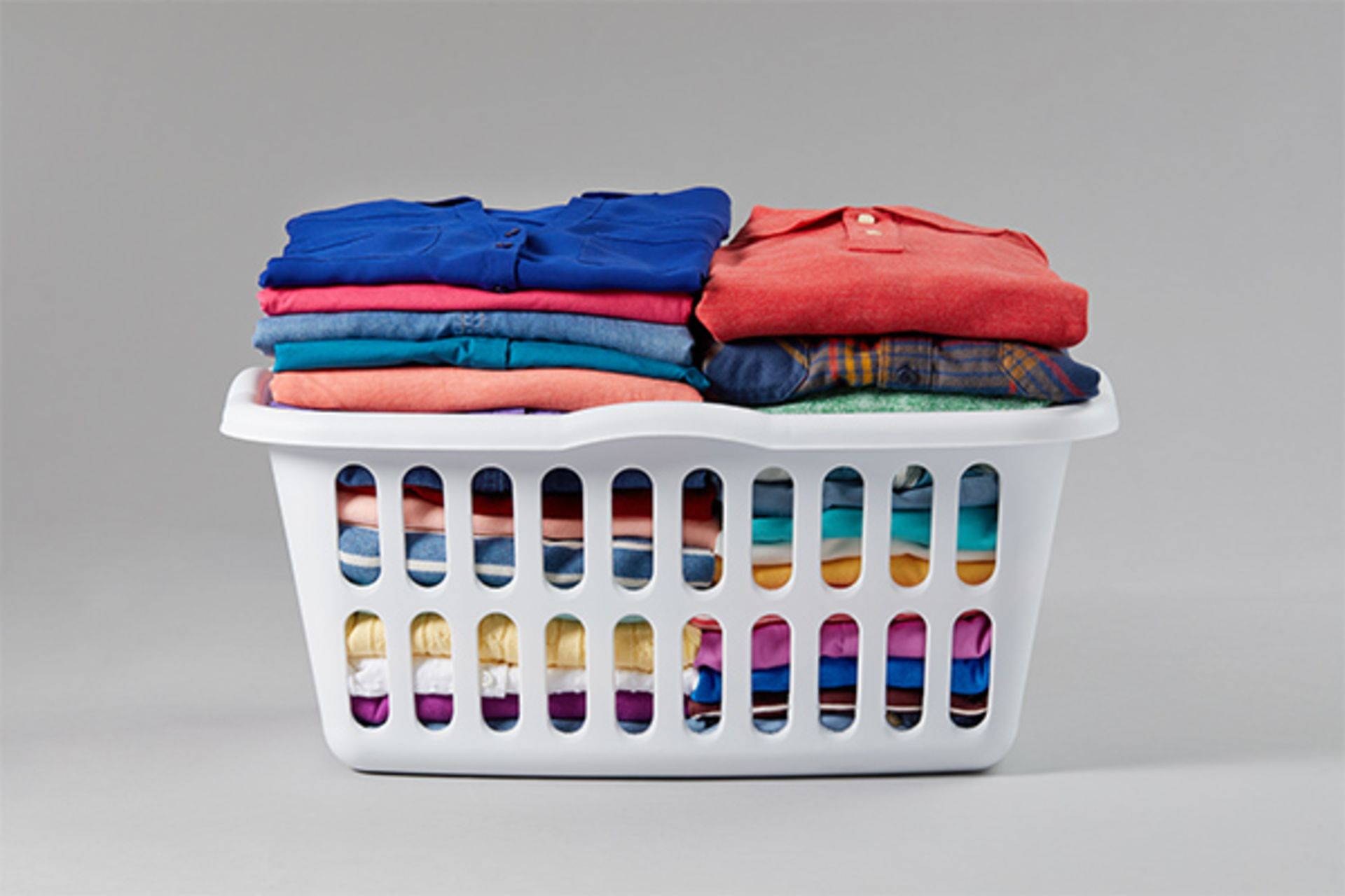 A laundry basket full of neatly folded, colored gaments