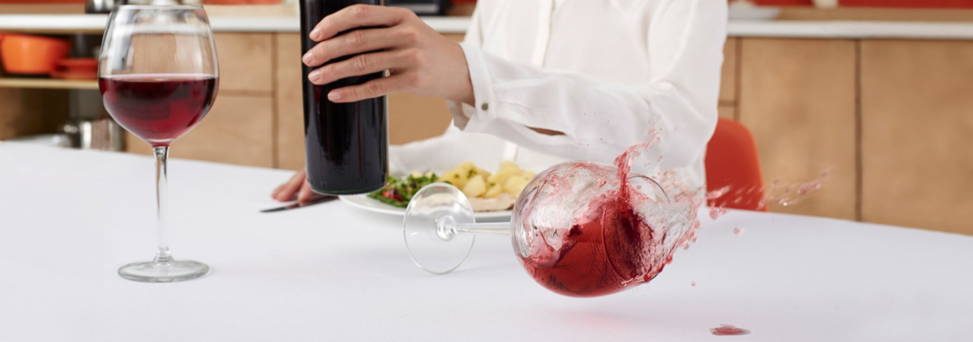 Red wine spilling onto a white table