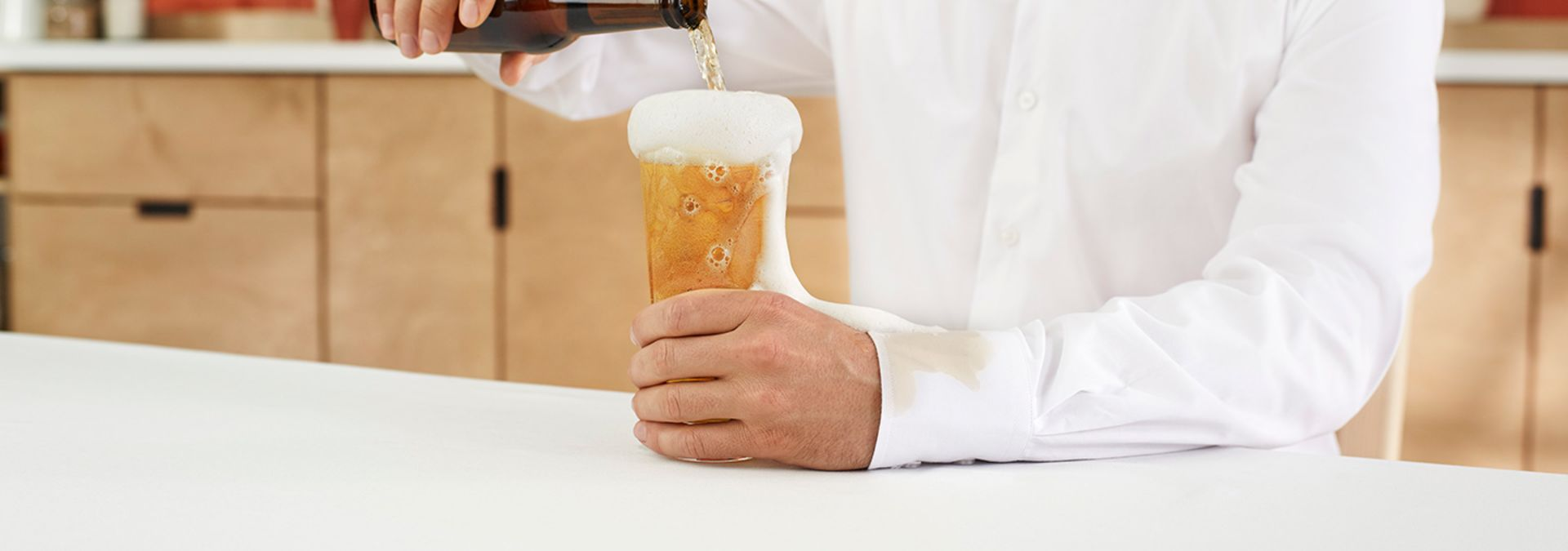 A person in a white shirt pouring beer into a glass