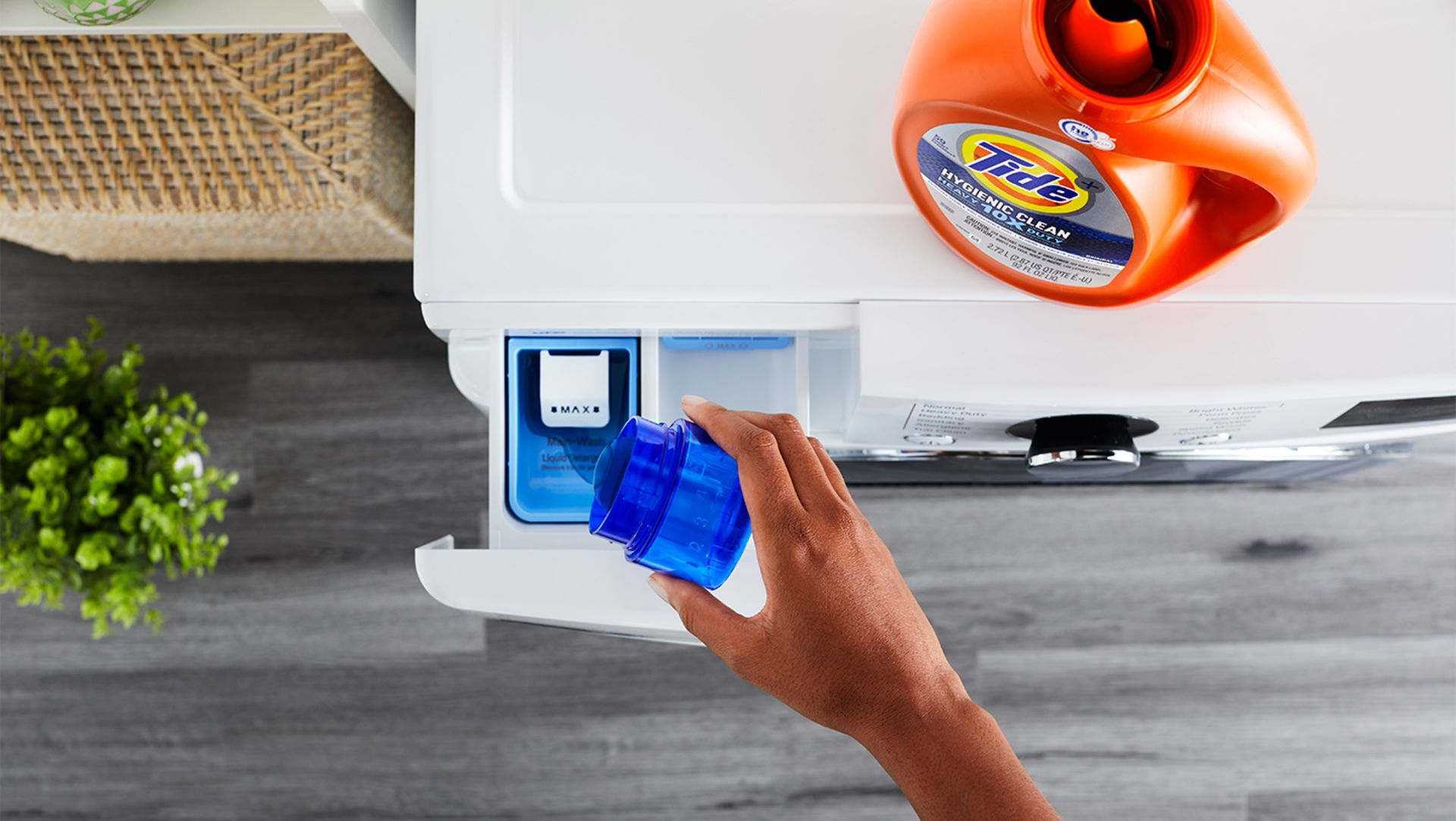 A person pouring Tide liquid detergent into the detergent dispenser