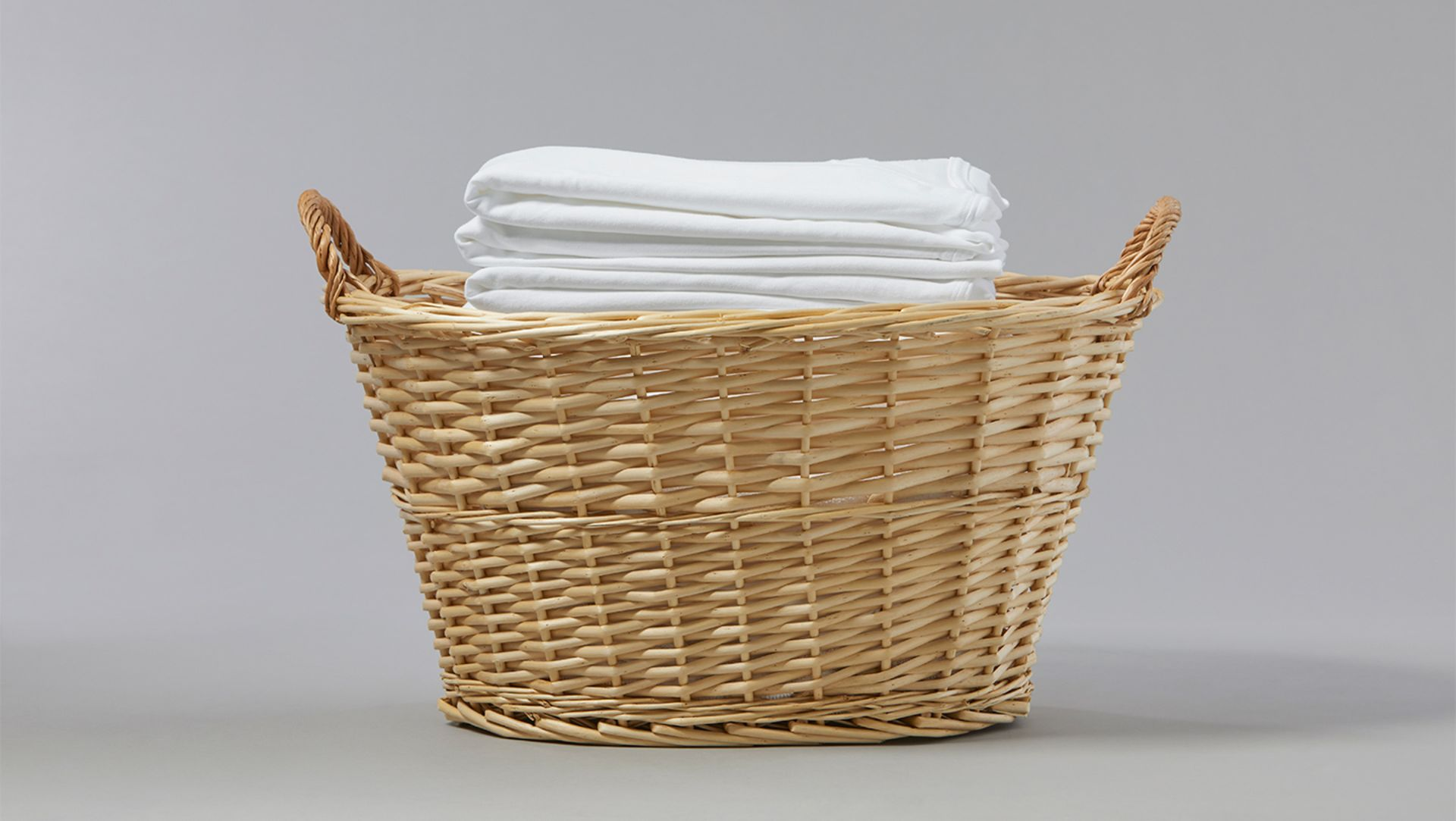 A woven laundry basket full of neatly folded, white garments