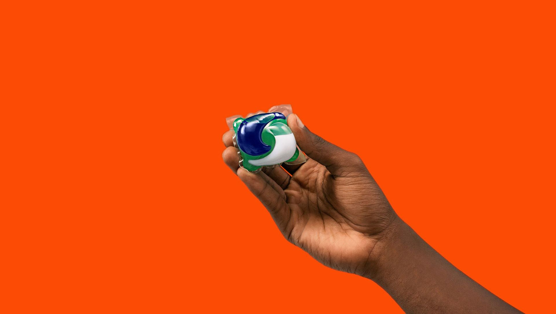 A person holding one Tide PODS washing capsule