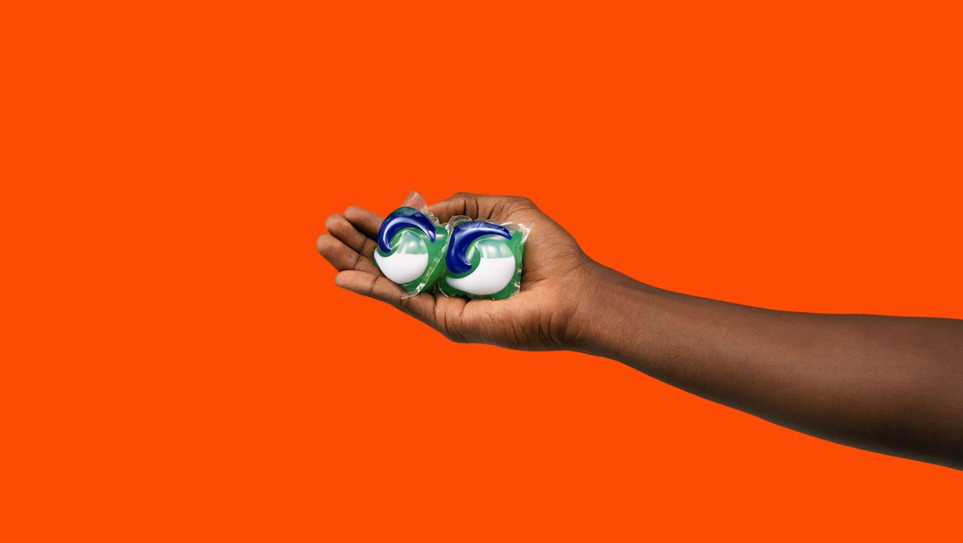 A person holding 2 Tide PODS washing capsules